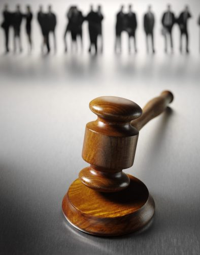 A team of business or law people standing in the background on a stainless steel background with a wooden gavel and block with copy space.